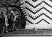 """Storie dietro le immagini - E' scritto sull'acqua... A Roma, la street art è diventata negli ultimi anni un interessante strumento espressivo. Dunque basta attendere """"l'attimo decisivo"""" e una qualunque forma d'arte può dare emozioni se si interseca anche con una parte del reale. Ecco crearsi una storia, una paradossale situazione in cui è il cane a rallentare per voler leggere l'epigrafe scritta sulla tomba del poeta inglese John Keats, al cimitero Acattolico di Testaccio, mentre i due anziani non paiono interessati all'incedere del tempo! Oggi quel graffito non c'è più, delebile come vuol essere la street art,ma indelebile come la fotografia riesce ad essere."""