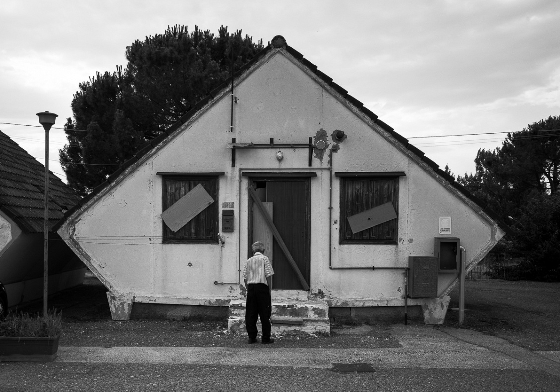 A man stands in front of one of the houses in the red zone of Bucaletto.